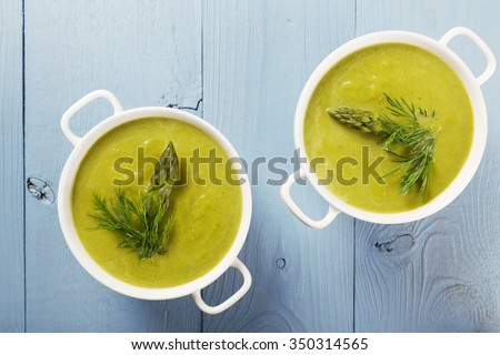 Delicious soup with asparagus, served in white bowls. - stock photo