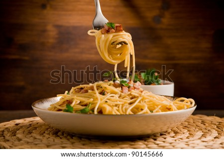 Delicious spaghetti with bacon and egg called alla carbonara on wooden table