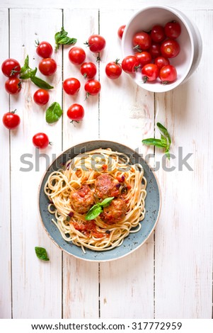 Delicious spaghetti with meatballs and tomato sauce on a plate. Serving on a white rustic wooden table. An Italian-American dish. Top view - stock photo