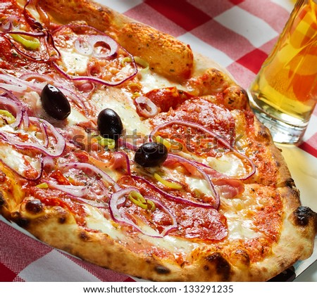 Delicious spicy pizza pepperoni with olives and glass of beer - stock photo