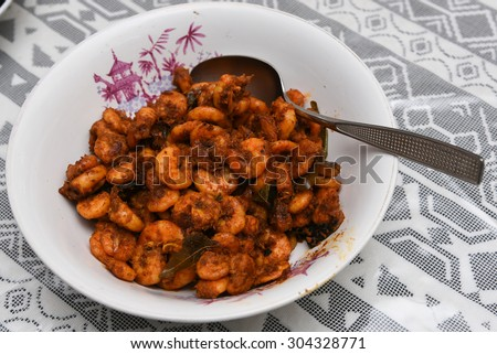 delicious spicy shrimp/prawns fried in a white bowl with spoon on a white textile background, Kerala India. South Indian cuisine. Good side dish for rice,appam, puttu. food served backwaters houseboat - stock photo