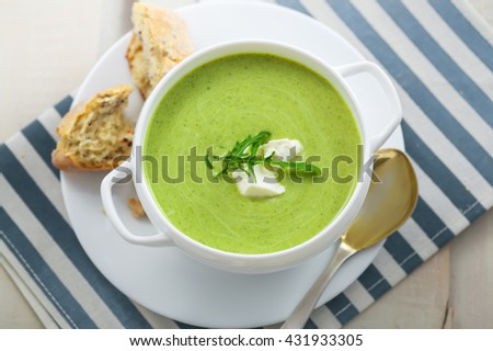 Delicious spinach cream soup with rye bread on a table. International meal. Top view. - stock photo
