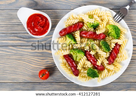 delicious spiral pasta salad with broccoli and grilled sausages decorated with dill on a white dish with tomato sauce in a gravy boat, top view  - stock photo