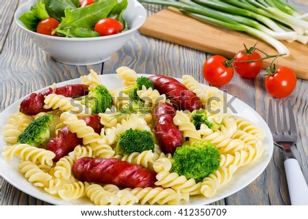 Delicious Spiral Pasta salad with  broccoli and grilled sausages on a white dish with fresh tomato and sorrel green salad,  spring onions on a cutting board on the background, close up  - stock photo
