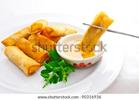 delicious springrolls with sweet plum sauce, one piece is held by chopstick - stock photo