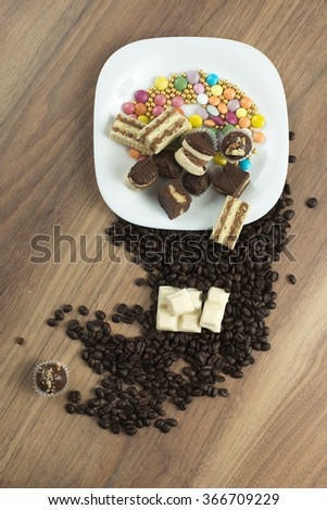 Delicious stack of sweet cookies, white chocolate and coffee bean on wooden table - stock photo