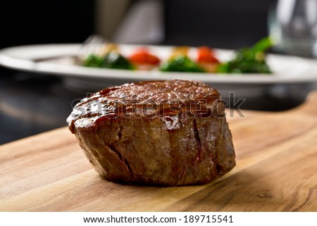 delicious steak on wooden kitchen board - stock photo