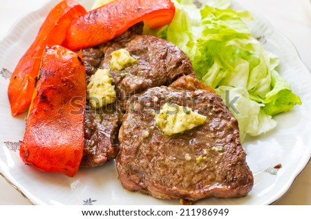 Delicious steak with garlic butter - stock photo