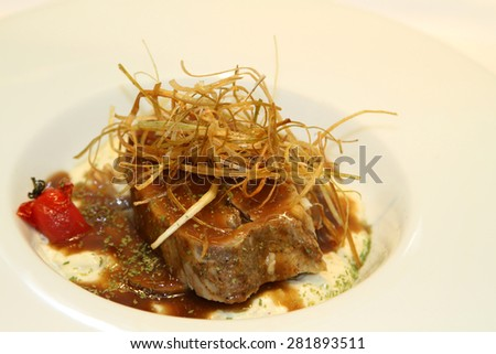 Delicious steak with sauce served in a white plate. - stock photo