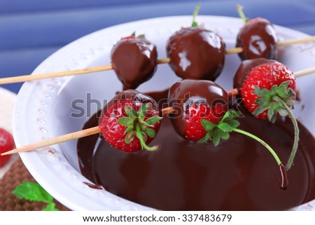 Delicious strawberries in chocolate in a bowl on wooden table - stock photo