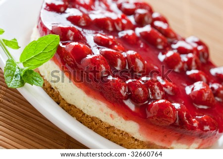 Delicious strawberry cheese cake with fresh mint on a white plate - stock photo