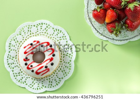 Delicious strawberry donut, served on a white napkin, decorated with strawberry.Green background. Horizontal image. Top view. View from above - stock photo