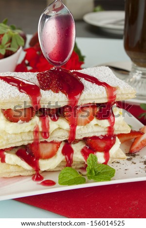 Delicious strawberry mille feuille with strawberry syrup being poured on top. - stock photo
