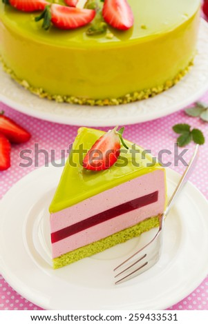 Delicious strawberry-pistachio mousse cake with a smooth glaze. - stock photo