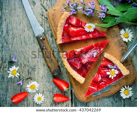 Delicious strawberry tart on old wooden background with summer flowers top view toning - stock photo