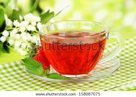 Delicious strawberry tea on table on bright background