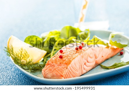 Delicious succulent portion of grilled or oven-baked fresh salmon fillet served with a leafy green salad and slice of lemon for flavoring - stock photo