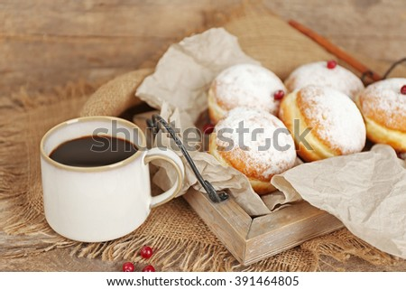 Delicious sugary donuts with red currant on wooden tray with parchment closeup - stock photo