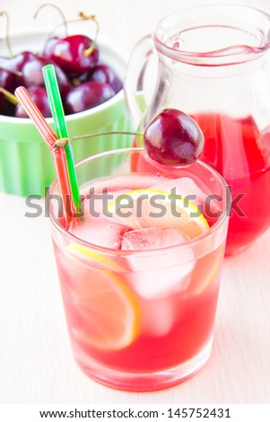 Delicious summery sweet berry juice of cherry in glass and carafe