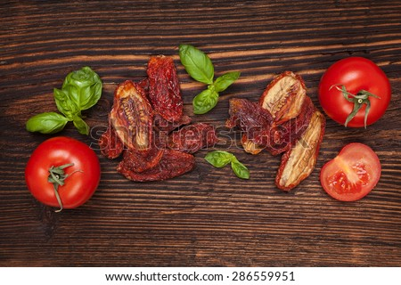 Delicious sundried and fresh tomatoes on brown wooden vintage textured background, top view. Traditional mediterranean kitchen. - stock photo