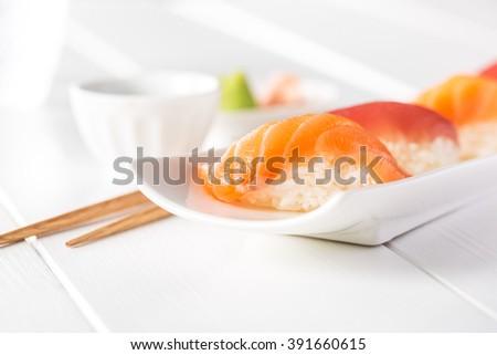 Delicious sushi nigiri of salmon and tuna on a white wooden table. - stock photo