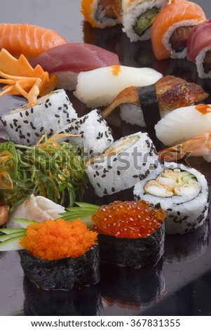 delicious sushi roll bar close up on black background - stock photo