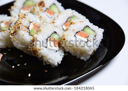 Delicious sushi rolls on a black plate with wasabi. - stock photo
