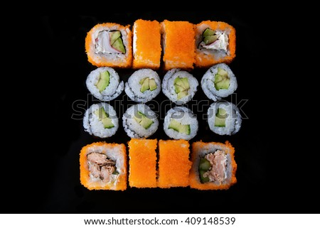 Delicious sushi rolls on black background