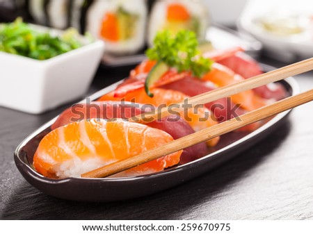 Delicious sushi rolls served on black plate and stone - stock photo