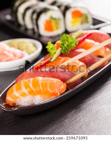 Delicious sushi salmon rolls served on black plate and stone - stock photo