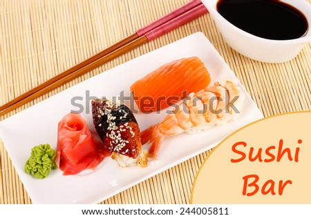 Delicious sushi served on plate on bamboo mat with space for your text - stock photo
