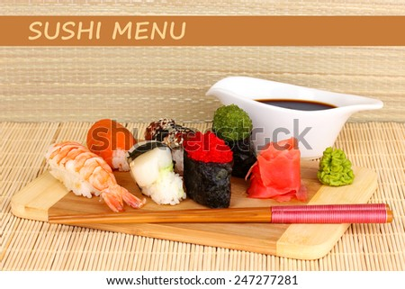 Delicious sushi served on wooden board on bamboo mat with space for your text - stock photo