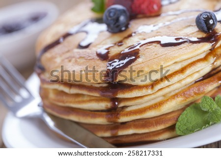 Delicious sweet American pancakes on a plate with fresh fruits and addons. - stock photo