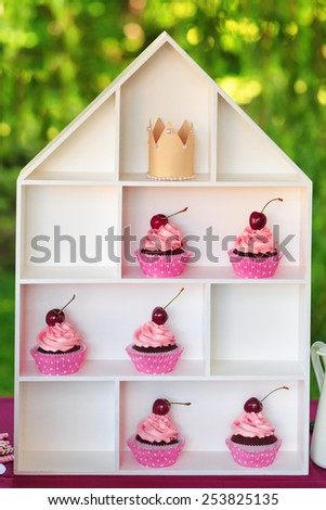Delicious sweet buffet with cupcakes on creative white stand - stock photo