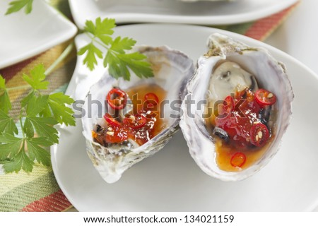 Delicious sweet chili oysters with parsley ready to serve.