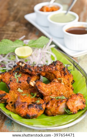 Delicious tandoori chicken starter, served with lime, onion, mint, yoghurt and sauces, on a banana leaf base. - stock photo