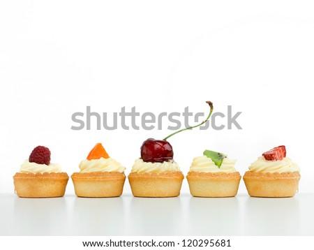 delicious tart arranged in line with raspberry cherries kiwi strawberry apricot white background izolated - stock photo