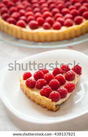 Delicious tart with custard and fresh raspberries. Slice - stock photo