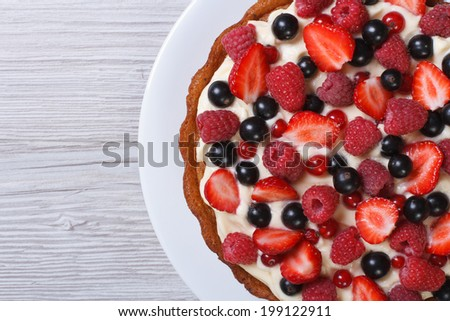 Delicious tart with fresh strawberries, raspberries and currants close-up on the table. top view horizontal  - stock photo