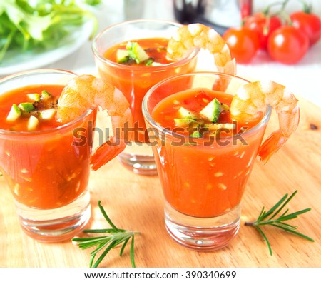 delicious tasty cold tomato soup gazpacho with avocado and prawns in portion glasses on wooden board, closeup, horizontal - stock photo