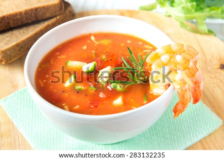 delicious tasty cold vegetable tomato soup gazpacho with shrimps (prawns) and rosemary in white bowl on wooden background, closeup, horizontal - stock photo