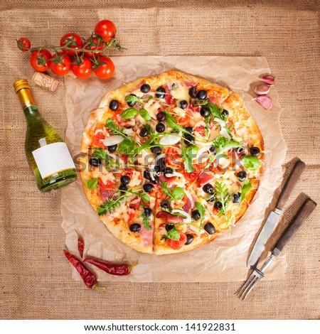 Delicious tasty pizza, fresh tomatoes, garlic, bottle of white wine and wooden cutlery on brown background, top view. Rustic country style italian eating concept. - stock photo