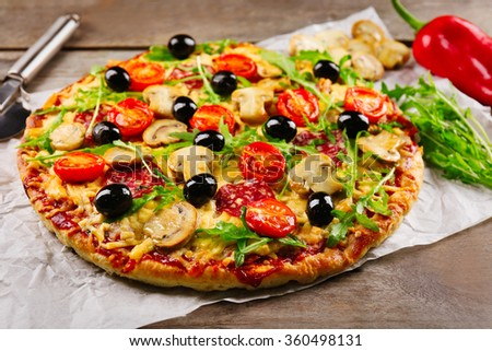 Delicious tasty pizza with cutter and ingredients on wooden table