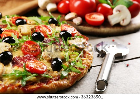 Delicious tasty pizza with cutter and ingredients on wooden table - stock photo