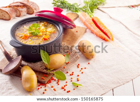 Delicious thick vegetable stew or soup in a pot surrounded by scattered fresh vegetables and ingredients in a rustic kitchen - stock photo