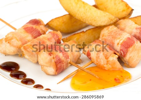 Delicious thin rolls of bacon with slices of fried potatoes and sauce on a plate - stock photo
