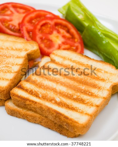 Delicious toasts with sliced tomatoes and green peppers. - stock photo