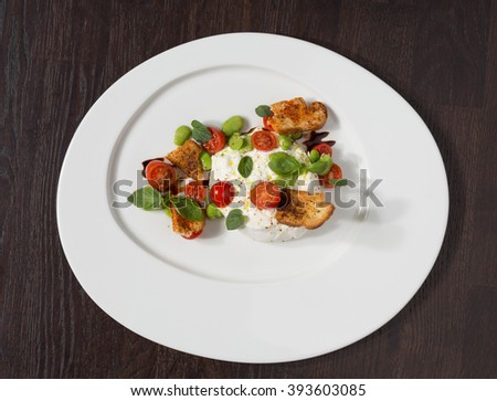 Delicious tomato and mozzarella cheese salad caprese, served on a white plate, with basil, croutons and balsamic vinegar. - stock photo