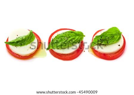 Delicious tomato and mozzarella salad over white background - stock photo