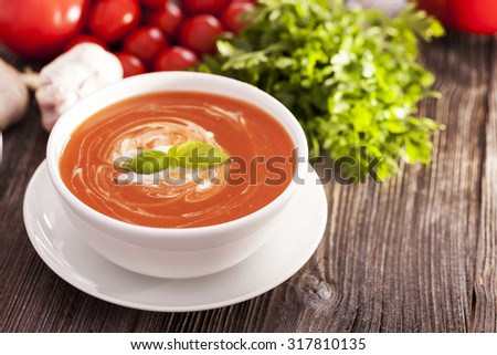 Delicious tomato soup with aromatic spices on a wooden table. Studio shot